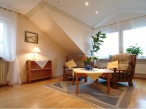 Ausstattung des Wohnzimmers mit Dachschräge, Tisch und zwei Sesseln